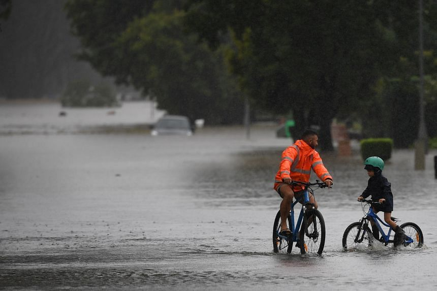 People ride bicycles on the flooded Old Hawkesbury Road in Australia on March 22, 2021.
