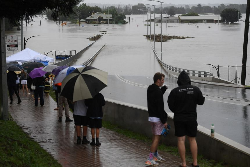 Onlookers watch the submerged New Windsor Bridge at Windsor in Sydney on March 22, 2021.