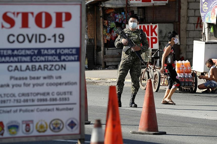 Security personnel manning a checkpoint at the border between Metro Manila and Cavite province in the Philippines yesterday. Leisure travel out of Metro Manila and four nearby provinces, including Cavite, has been banned in a bid to curb an outbreak
