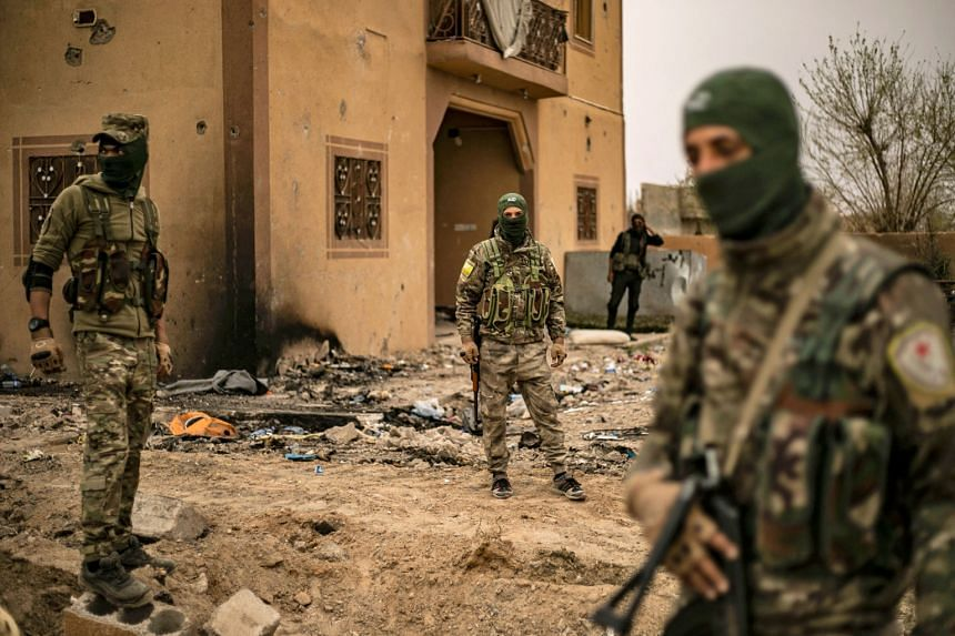 Members of the Syrian Democratic Forces in the village of Baghouz in Syria's eastern Deir Ezzor province near the Iraqi border on March 24, 2019.