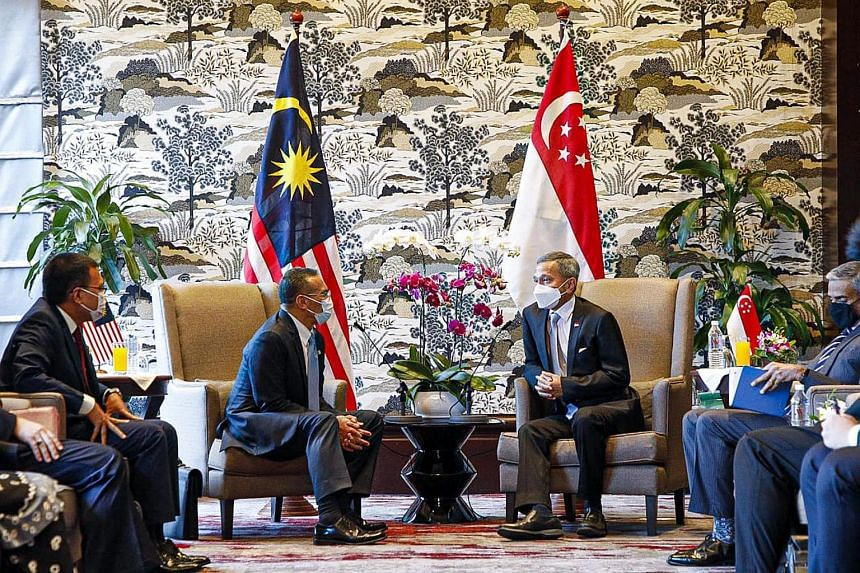 Singapore's Foreign Minister Vivian Balakrishnan (right) meeting with Malaysian counterpart Hishammuddin Hussein, in Kuala Lumpur on March 23, 2021.