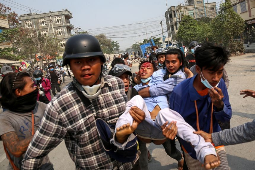 People carry an injured demonstrator during a protest against the military coup in Mandalay, on March 22, 2021.