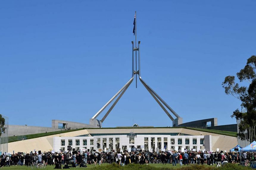 Protesters attend a rally against sexual violence and gender inequality in front of the Parliament House in Canberra, Australia, on March 15, 2021.