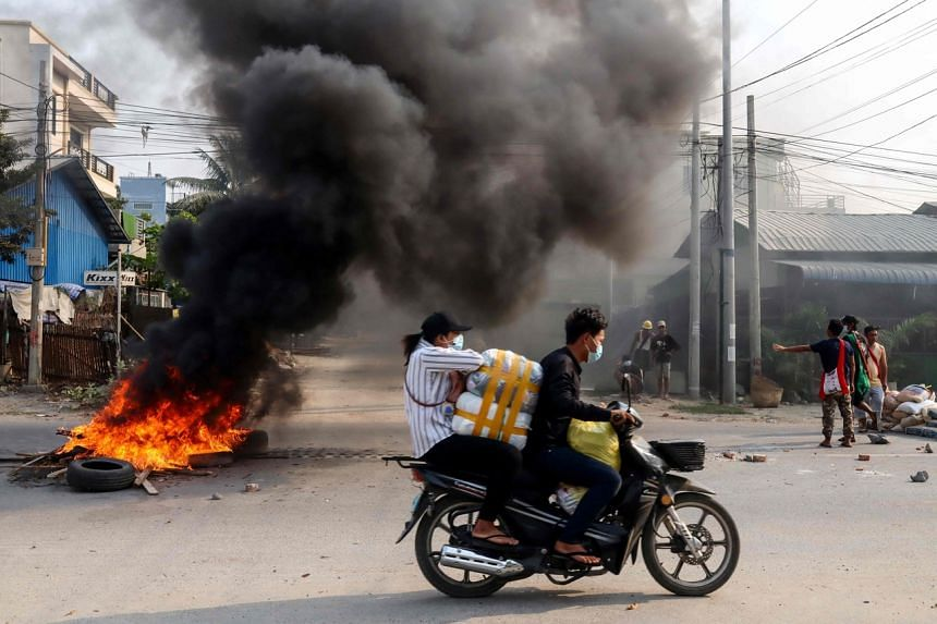 Motorists passing a burning barricade during a crackdown by security forces on demonstrations by protesters against the military coup in Mandalay, on March 22, 2021.