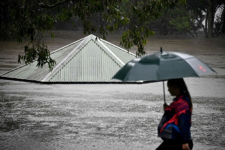 A woman walks past a flooded park along the overflowing Nepean river in Sydney, on March 21, 2021.