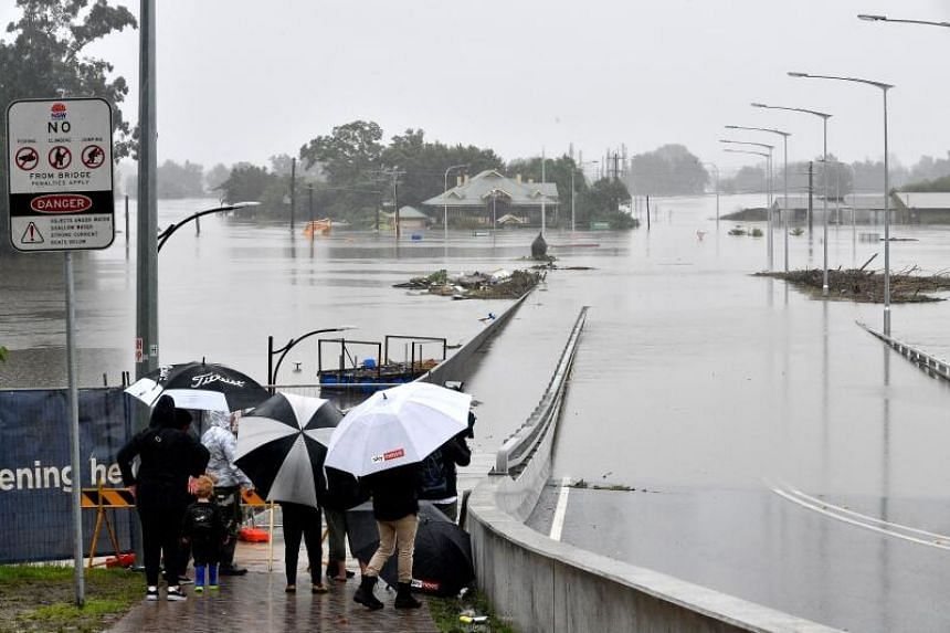 Residents look out at a flooded residential area in the Windsor area in northwestern Sydney on March 23, 2021.
