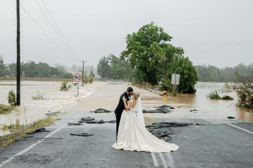 Mr Wayne Bell and Ms Kate Fotheringham kiss in front of a flooded bridge that had blocked their five-minute drive into town.