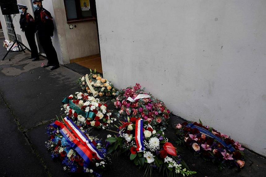 Flowers are laid outside Charlie Hebdo's former offices on Jan 7, 2021.