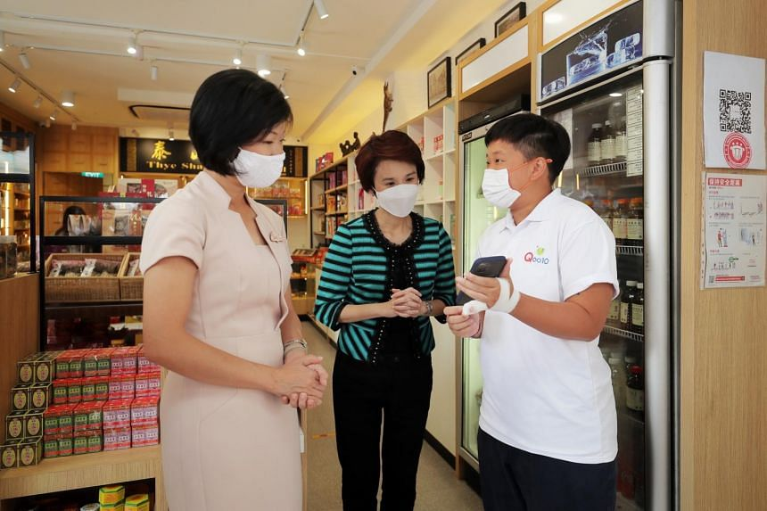 A Qoo10 representative showing an app to Senior Minister of State for Communications and Information Sim Ann (far left) and and Minister of State for Trade and Industry Low Yen Ling.