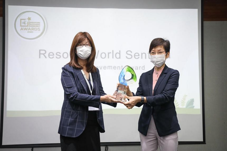 Minister for Sustainability and the Environment Grace Fu (right) presenting an award to Resorts World Sentosa's vice-president of procurement Loh Su Kim.