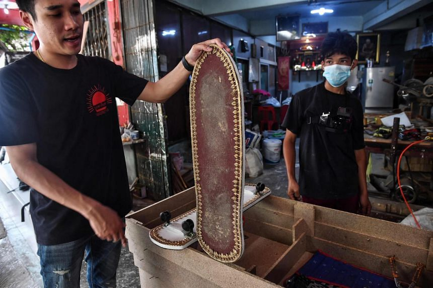 Coffin-maker Anusorn Yungyearn with a skateboard made from wood used for coffins at the Burapha coffin shop in Bangkok.