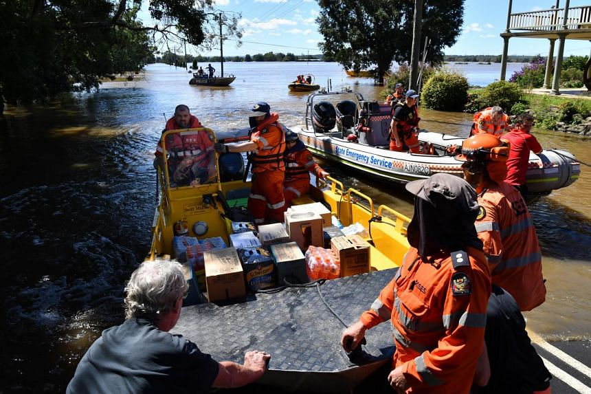 State Emergency Service, New South Wales police and local residents help load supplies onto police and SES boats on March 24, 2021.