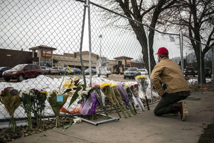 A mourner leaves flowers after a gunman opened fire at a King Sooper's grocery store in Boulder, Colorado, on March 23, 2021.