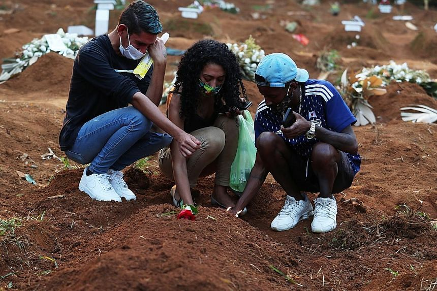 Relatives of a 65-year-old coronavirus victim paying respects at her grave at a cemetery in Sao Paulo this week. Brazil's new record number of daily Covid-19 deaths on Tuesday underlines the scale of the country's outbreak, which is spiralling out of