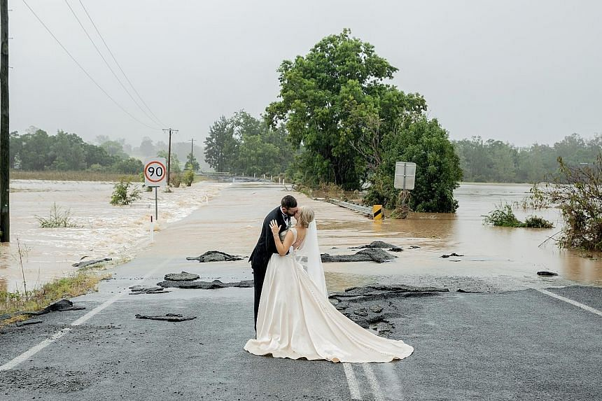 Newlyweds Wayne and Kate Bell in front of the flooded bridge in New South Wales that blocked Mrs Bell's way to her wedding venue on Saturday. She eventually arrived at the venue in a helicopter sent by a local TV station.