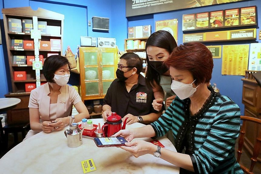 Chope's campaign sales manager Hazel Lee (second from right) showing Minister of State for Trade and Industry Low Yen Ling how to purchase a ChopeDeals voucher at Nanyang Old Coffee in South Bridge Road yesterday. With them are Senior Minister of Sta
