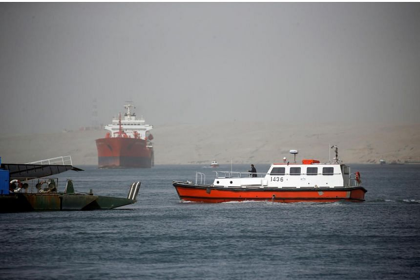 A patrol boat is seen as ships passing through the Suez Canal arrive in Ismailia, Egypt, on March 24, 2021.