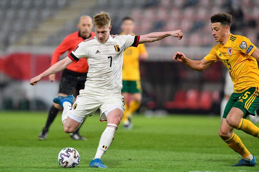 Belgium's Kevin De Bruyne (left) kicks the ball during the World Cup qualification football match against Wales, on March 24, 2021.