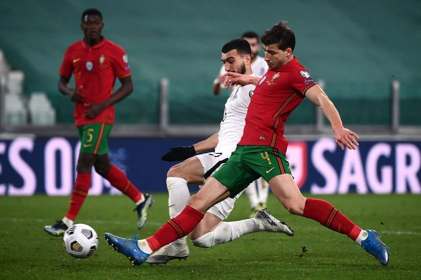 Azerbaijan's Mahir Emreli (left) vies with Portugal's Ruben Dias during the World Cup qualification football match on March 24, 2021.