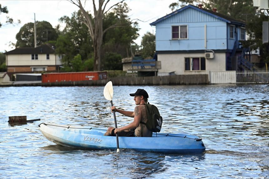 A local resident kayaks to his house in the suburb of Windsor near Sydney on March 24, 2021.