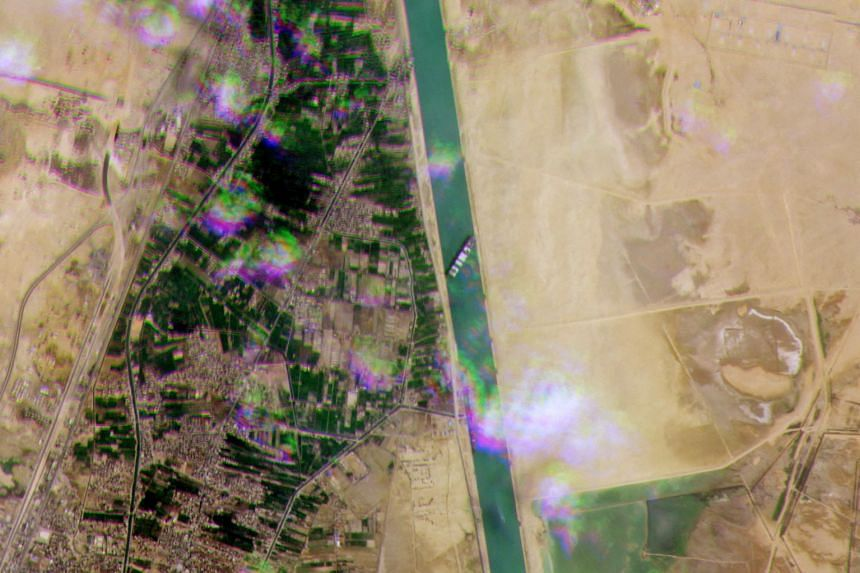 A satellite handout image shows the Ever Given container ship lodged sideways across the Suez Canal.