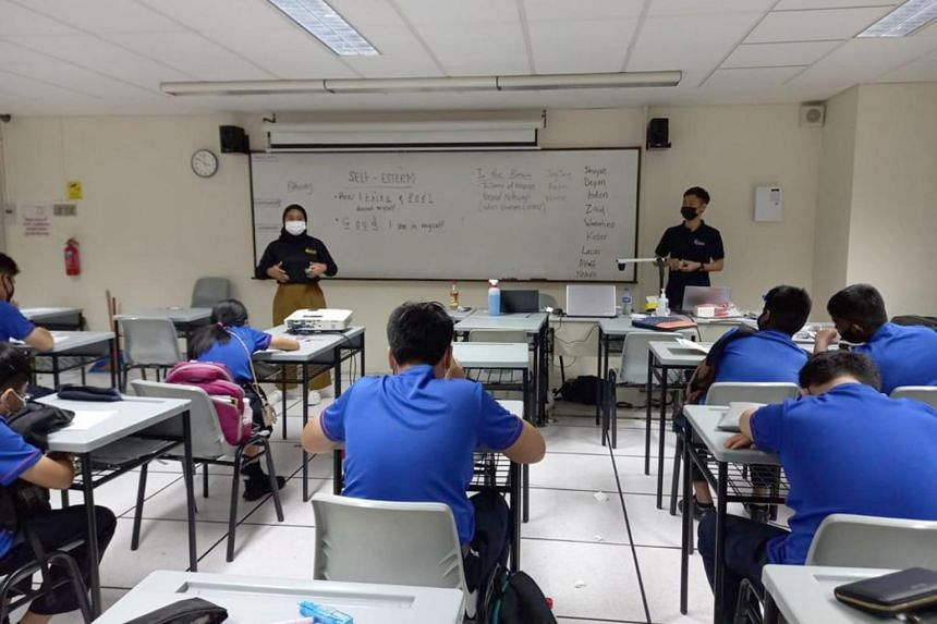 Ms Elfi Sufiyanti (standing, left) during a mentoring session with a group of secondary school students.