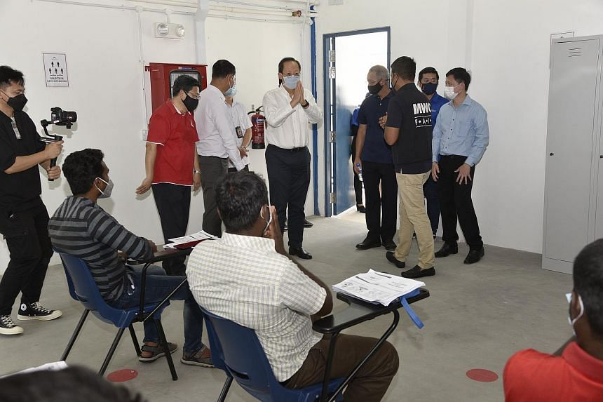 Second Minister for Manpower Tan See Leng (centre) greeting migrant workers at the migrant worker onboarding centre in Punggol on March 26, 2021.