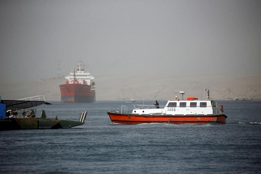 A patrol boat is seen as ships pass through the Suez Canal arrive in Ismailia, Egypt, on March 24, 2021.