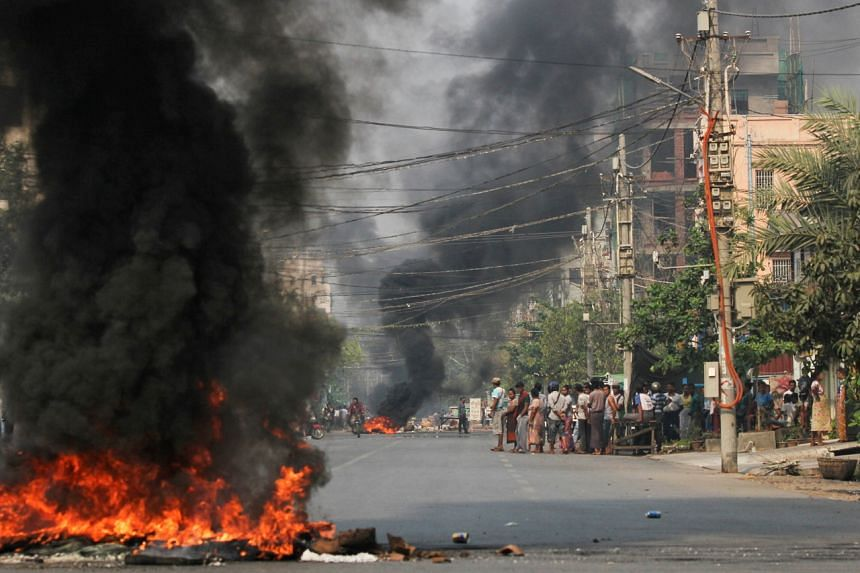 Tyres burn on a street as protests against Myanmar's military coup continue in Mandalay on March 27, 2021.