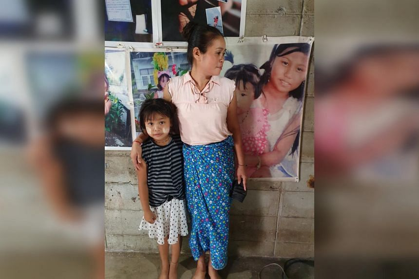 Jobless Myanmar migrant worker Cho Lwin with her younger daughter in their rented home in Thailand's Ranong province. On her left is a photo of her 16-year-old daughter who is in Myanmar.