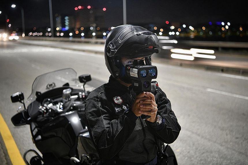LTA officers checking a vehicle for illegal modifications along Yishun Dam yesterday. From left: A Traffic Police officer using a police speed laser camera, a Land Transport Authority (LTA) officer using a tint inspection device on a vehicle and LTA