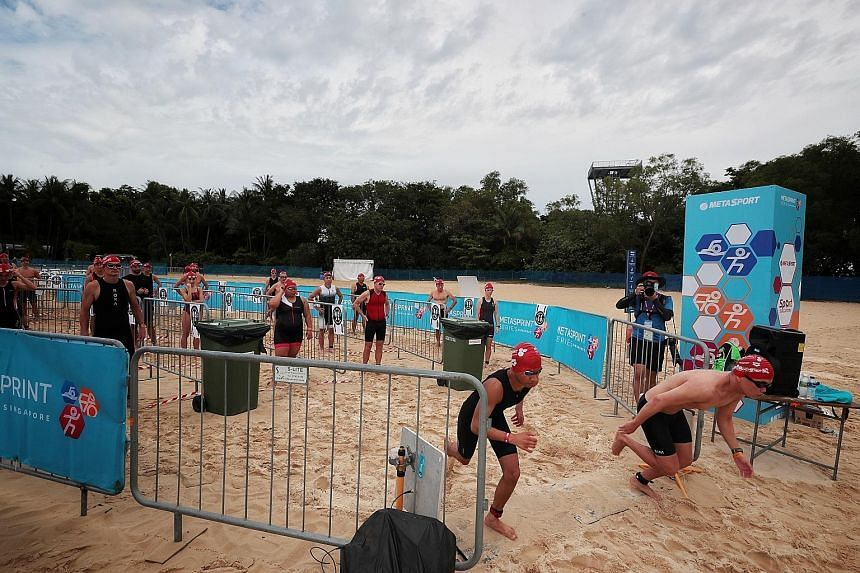Racers are flagged off two by two as they compete in the MetaSprint Series aquathlon at the Palawan Beach in Sentosa on March 27, 2021.