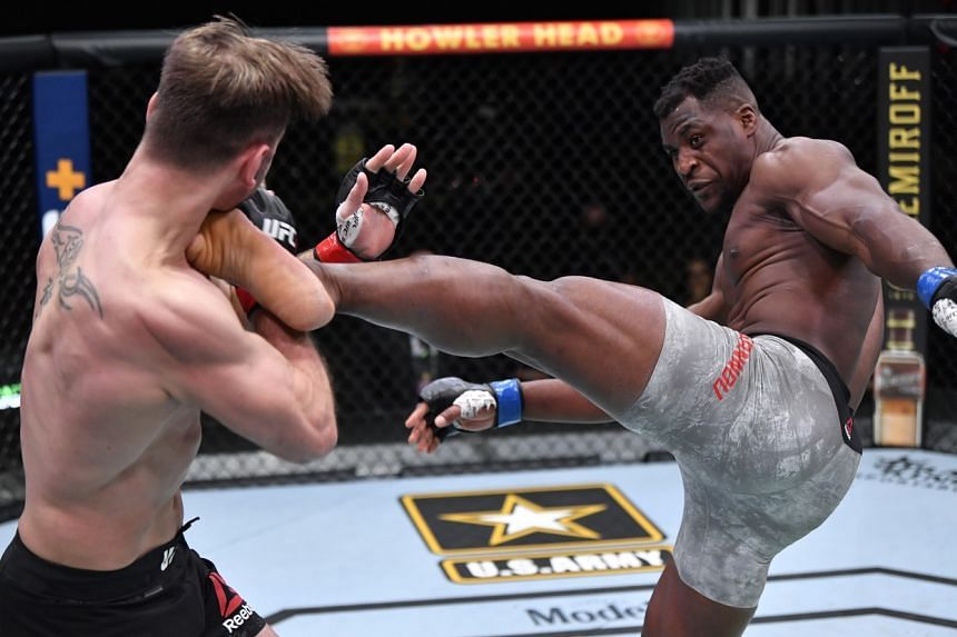 Francis Ngannou (right) kicks Stipe Miocic during the UFC 260 event at UFC APEX in Las Vegas, on March 27, 2021.