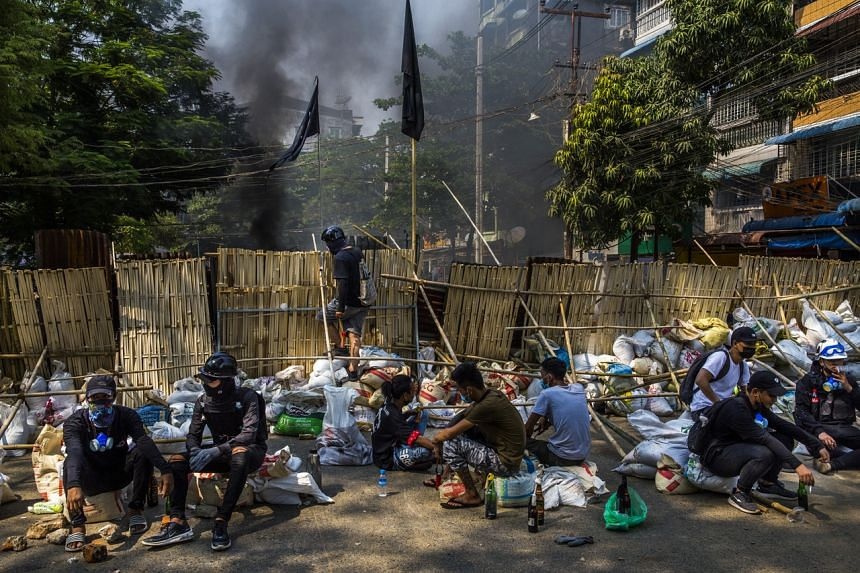 Protesters look out from behind makeshift barriers in Yangon on March 27, 2021.