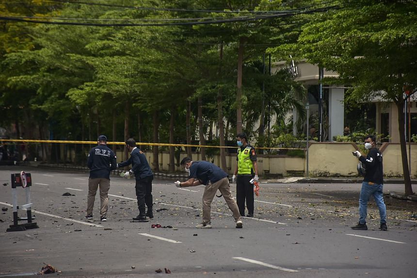 Indonesian forensic police examine the site after a suspected bomb exploded near a church in Makassar on March 28, 2021.