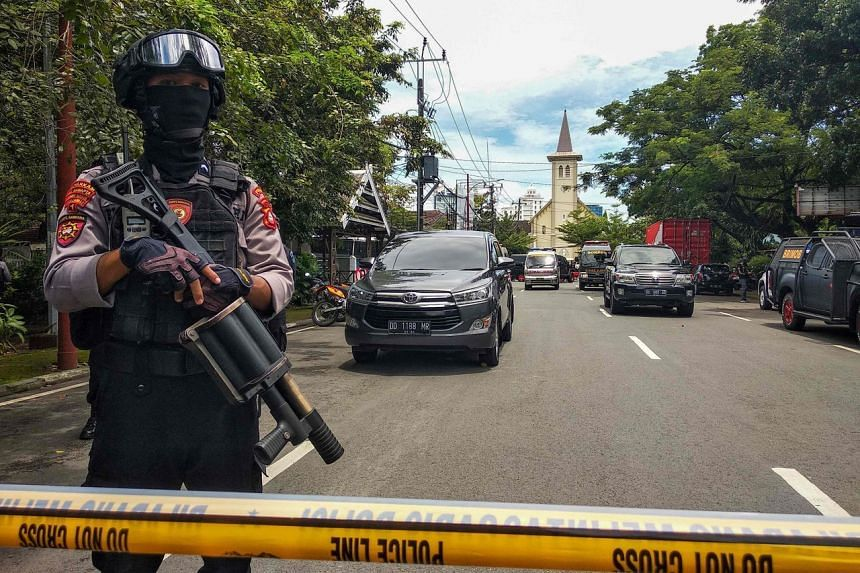 An Indonesian anti-terror policeman stands guard as police seal the area after an explosion outside a church in Makassar on March 28, 2021.