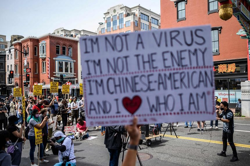 People listen to speakers as they participate in an 'Anti Asian Hate' rally in Chinatown in Washington, DC on March 27, 2021.