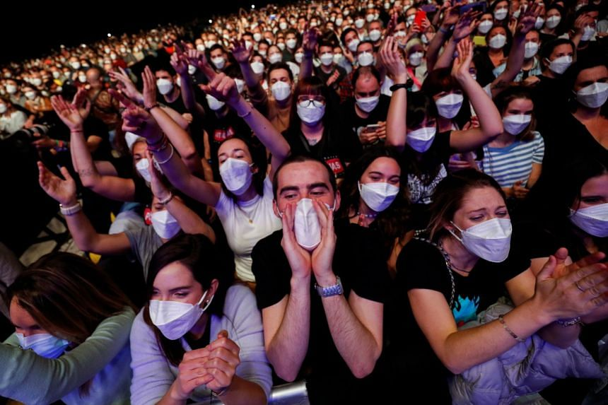 People wearing protective masks attend a concert at the Palau Sant Jordi  in Barcelona, on March 27, 2021.