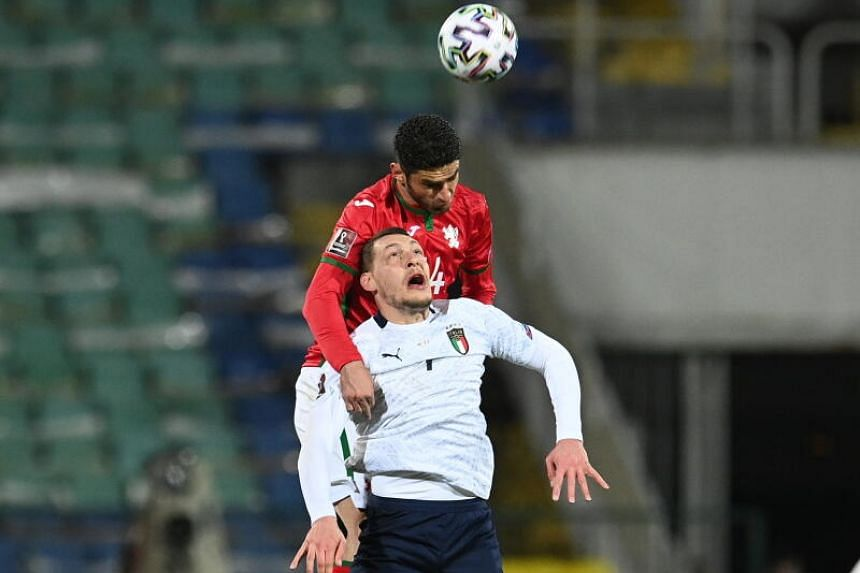 Italy's Andrea Belotti (front) fights for a high ball with Bulgaria's Daniel Dimov in Sofia, Bulgaria, on March 28, 2021.