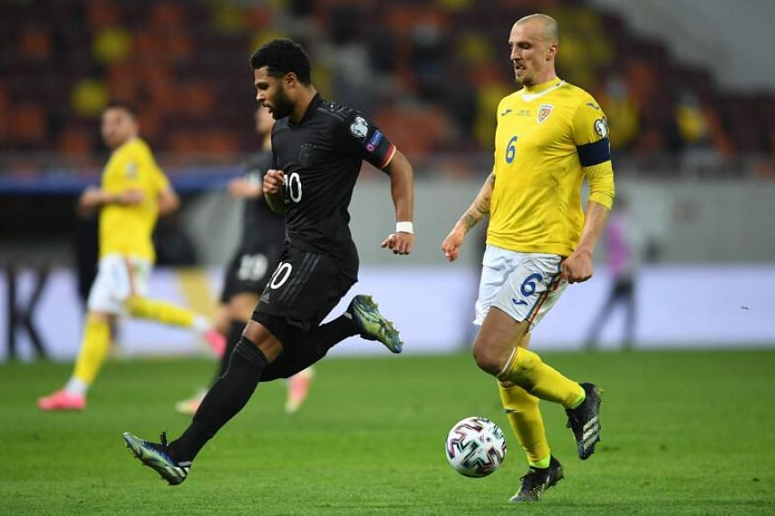 Germany's midfielder Serge Gnabry (left) and Romania's defender Vlad Chiriches vie for the ball on March 28, 2021.