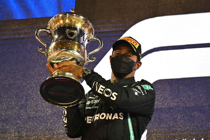 Lewis Hamilton raises his first-place trophy in Sakhir, Bahrain, on March 28, 2021.