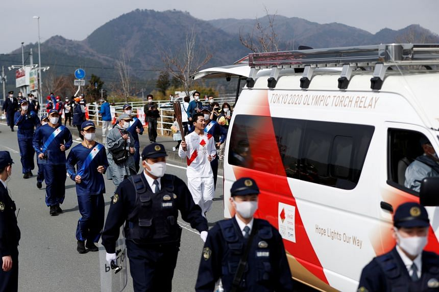 A torchbearer runs with a convoy during the Tokyo 2020 Olympic torch relay in Naraha, Fukushima, on March 25, 2021.