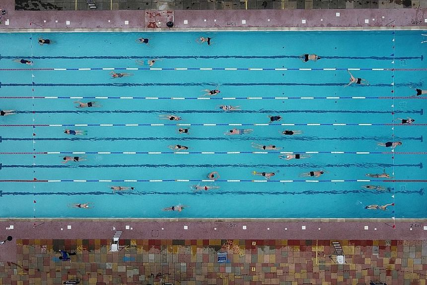 Swimmers taking to the waters yesterday in Hampton Lido in London, on the first day that outdoor pools were open following the easing of lockdown curbs amid the coronavirus pandemic in Britain.