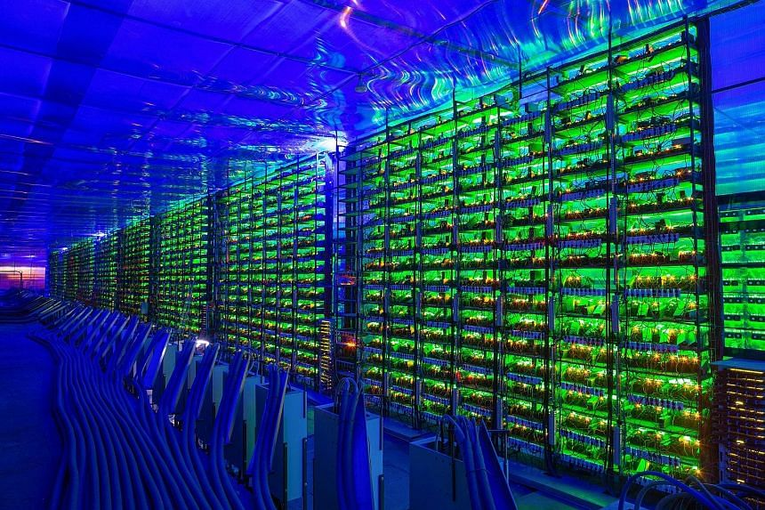 Left: Illuminated mining rigs operating inside racks at the CryptoUniverse cryptocurrency mining farm in Nadvoitsy, Russia, to produce virtual currency. Below: A bitcoin token. The price of bitcoin has jumped 700 per cent in the past year, hitting a