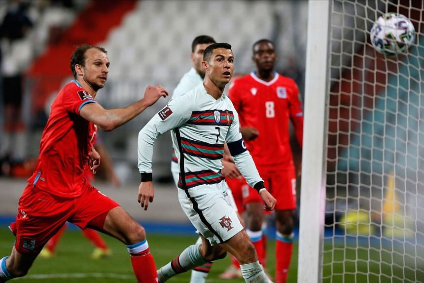 Portugal's Cristiano Ronaldo (centre) and Luxembourg's Lars Gerson (left) watch the ball hitting the net for Portugal's 3-1 lead.