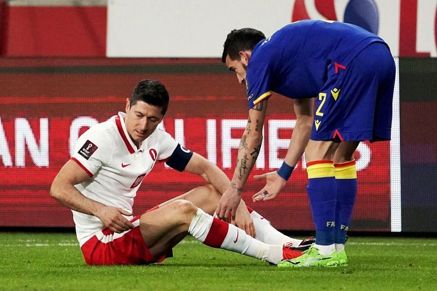 Poland's Robert Lewandowski reacts after sustaining an injury as Andorra's Cristian Martinez looks on.
