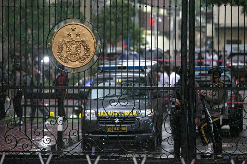 A police security team guards the entrance to the Indonesia National Police Headquarters in Jakarta on March 31, 2021, after gunfire was heard in the compound.