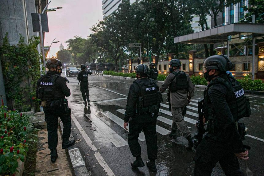 Police officers patrol outside the entrance of the Indonesia National Police Headquarters in Jakarta on March 31, 2021.