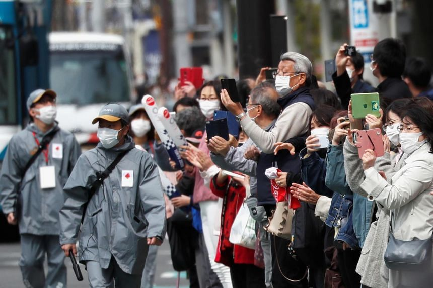 Spectators look on during the Tokyo 2020 Olympic torch relay on the second day of the relay in Fukushima, Japan, on March 26, 2021.