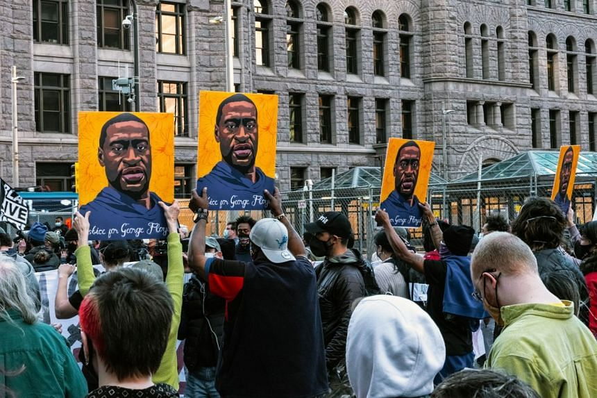 Protesters hold portraits of George Floyd on March 29, 2021, outside of the court building in Minneapolis.